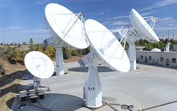 Networking technology shown through four ground antennas pointed at the sky