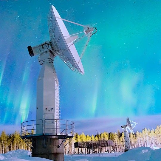 Two remote sensing antennas mounted in a snowy field pointed at a beautiful, blue streaky sky