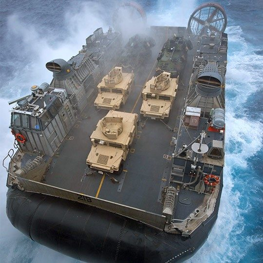 Aerial view of giant military hovercraft with mobile antennas at sea carrying three humvees