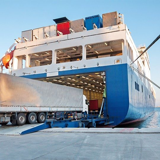 Large cargo truck driving off the dock onto a giant cargo ship