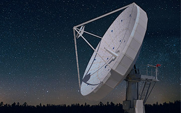 White ground satellite antenna against a starry night sky