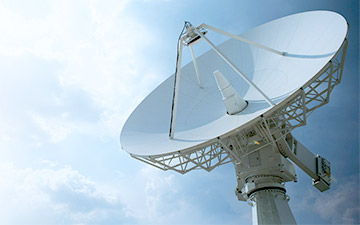 White ground station satellite communication antenna against a light blue sky with clouds