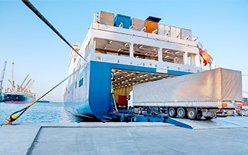 Semi-trailer truck driving onto a large cargo ship