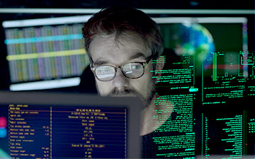Man wearing glasses looking at projected computer data