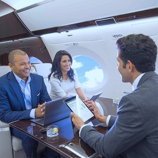 Two men and one woman sitting at a table in a private jet, using tablets and a laptop connected with WiFi for private aircraft