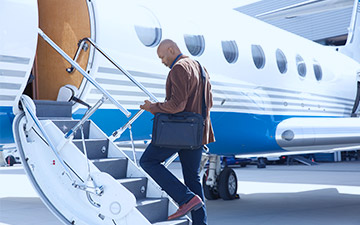 Male business traveler with a laptop bag on his shoulder is looking at his smartpone while walking up the stps of a private jet