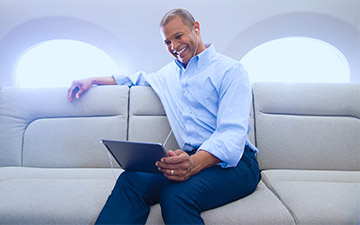 Smiling man sitting in a private jet wtih private jet internet, dressed in a blue button up shirt looking at a tablet