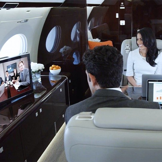 Professional man and woman sit across from each other at a table on a private jet pariticipating in a video conference