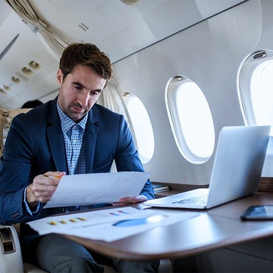 Man sitting at a table in a private jet working on his laptop and reading paperwork