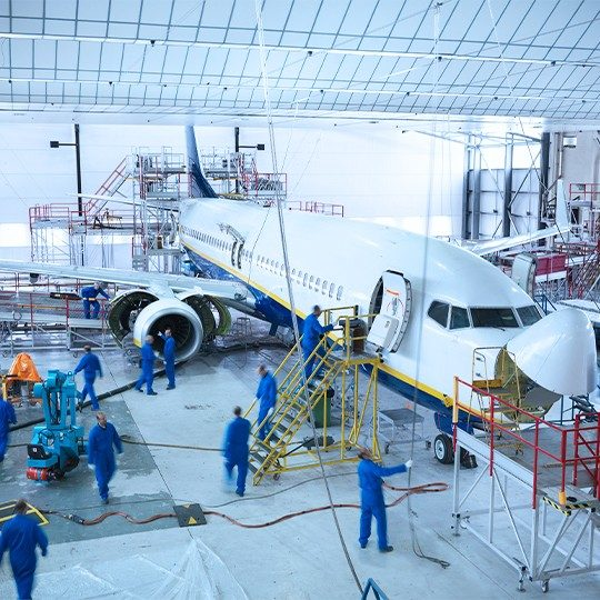 Team of airplane technicians working on a commercial plane inside a hanger