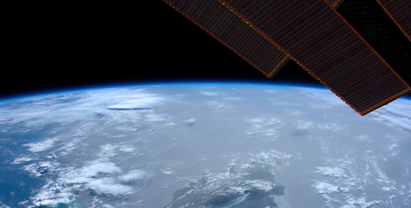 Edges of the solar array of a Viasat satellite in space orbiting around the Earth