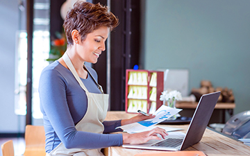 Woman with short hair in a blue shirt, wearing an apron, working from her laptop connected by a commercial hotspot