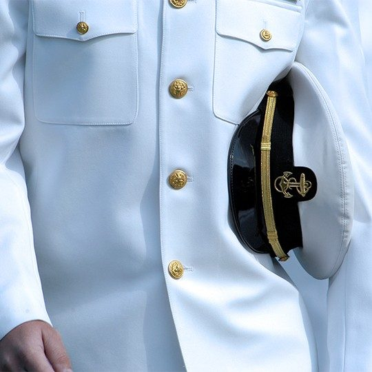Close-up of a man dressed in white Navy uniform with a Navy hat tucked under his arm