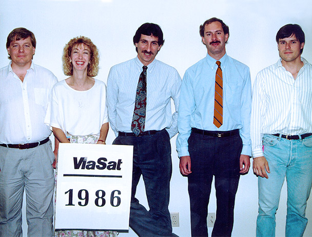Founders Mark Dankberg, Steve Hart and Mark Miller plus two Viasat employees standing behind a sign that reads 'Viasat 1986'