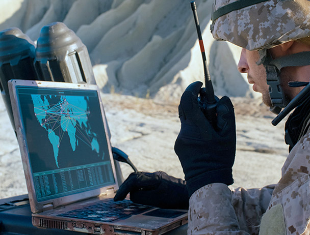 Soldier talking on a handheld satellite radio, looking at a map on a laptop