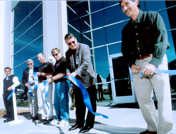 Mark Dankberg and five Viasat employees cutting a blue ribbon in front of the new Carlsbad, CA campus