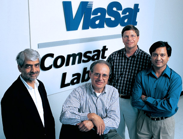 Four Viasat employees smiling at the camera in front of a Viasat Comsat Lab sign