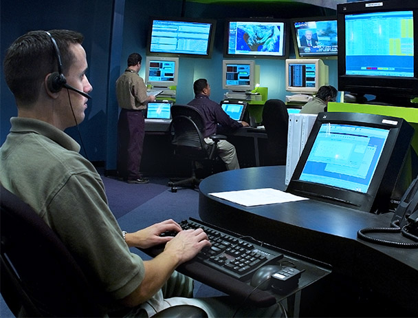 Three Viasat network operations employees monitoring data on computer and TV monitors