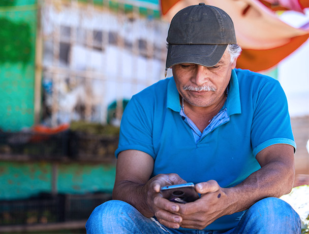 Man wearing a hat and blue polo, sitting outside of a store looking at his smartphone
