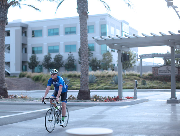 Viasat employee riding his bike across the crosswalk at the corporate Carlsbad campus