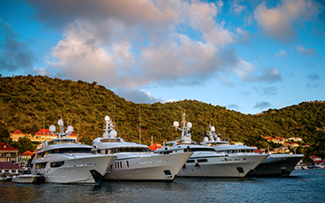 Four charter yachts sitting in a bay next to a luscious mountain