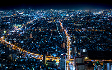 Aerial view of a large city at night beaming with city lights