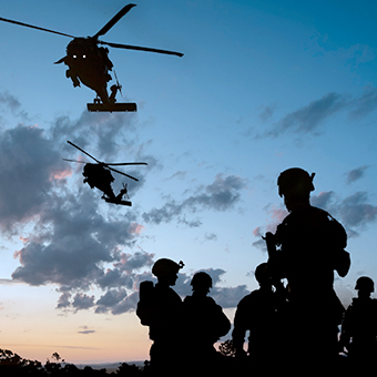 Silhouettes of five army men in the field at dusk with two helicopters flying above