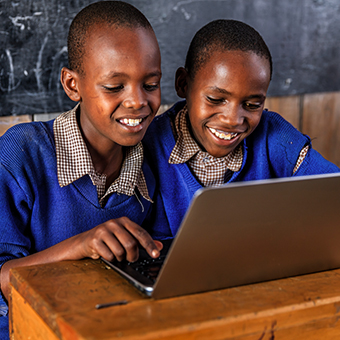 Two school boys in Africa smiling at a laptop