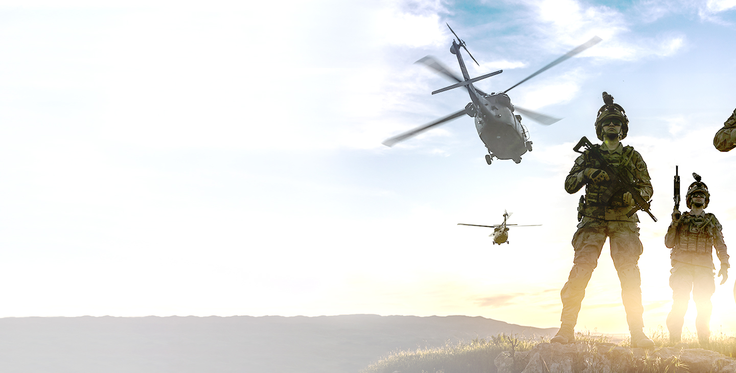 Two soldiers dressed in army gear holding military weapons wtih two helicopters flying off into the sunset