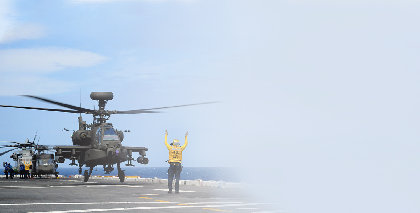 Ground helicopter crew member wearing a yellow jacket signaling a helicopter taking off from an aircraft carrier