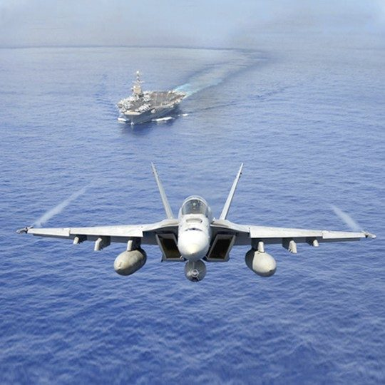 Aircraft carrier on the ocean and a fighter aircraft flying above