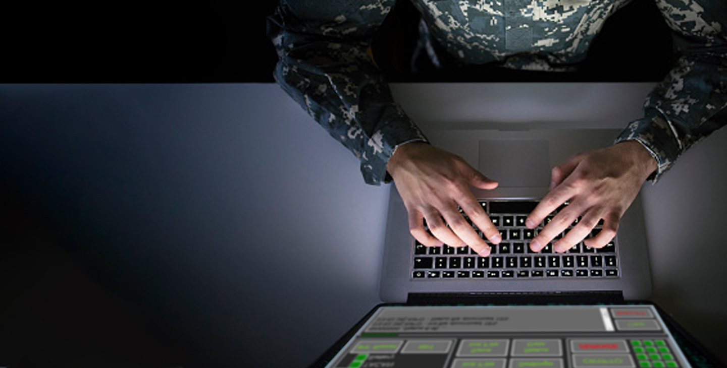 Overhead view of a man wearing army greens typing on a laptop using Link 16 software