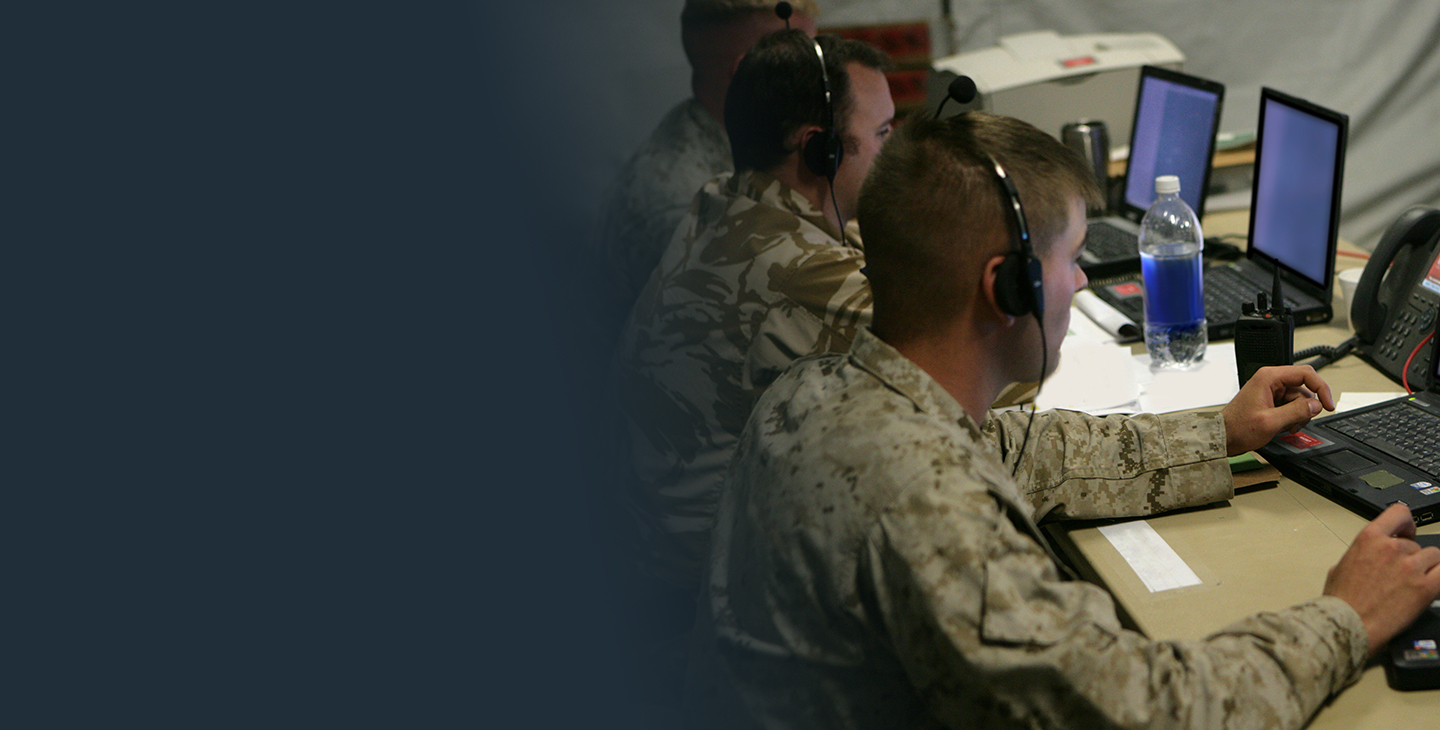 Three male warfighters looking at a laptop in a tactical operations center