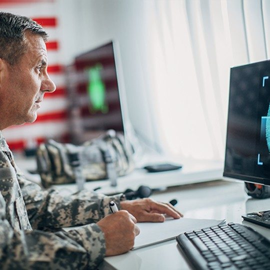 Man in an army uniform writing on a piece of paper while looking at a computer protected with an Eclypt hard drive