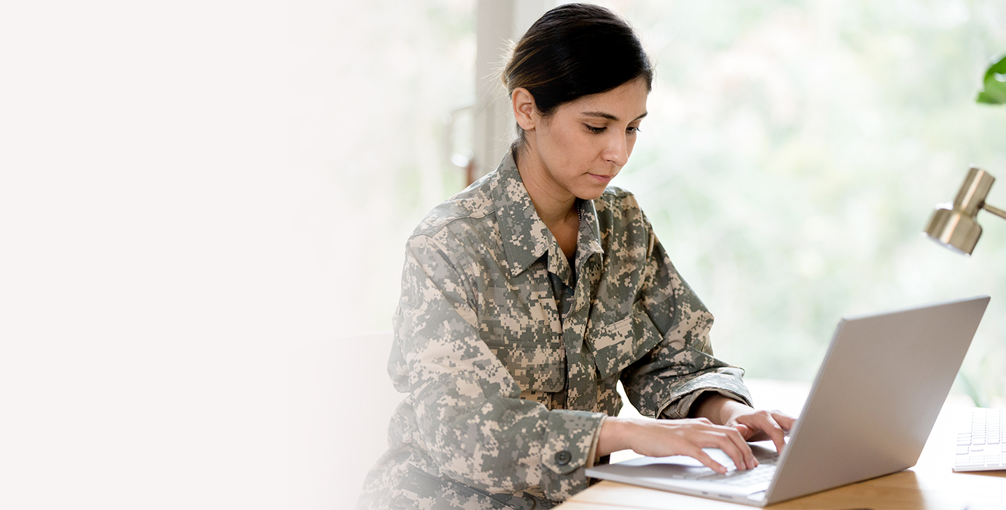 Dark-haired woman in army fatigues sitting at a table working on a laptop protected with the Viasat data at rest ecryption solution