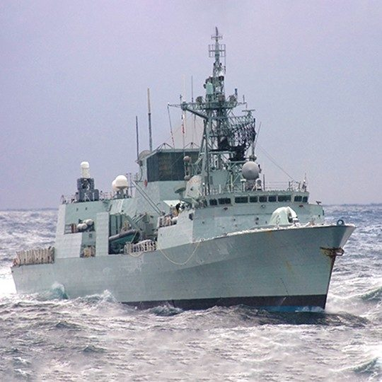 Military ship with UHF SATCOM communication systems navigating rough waters