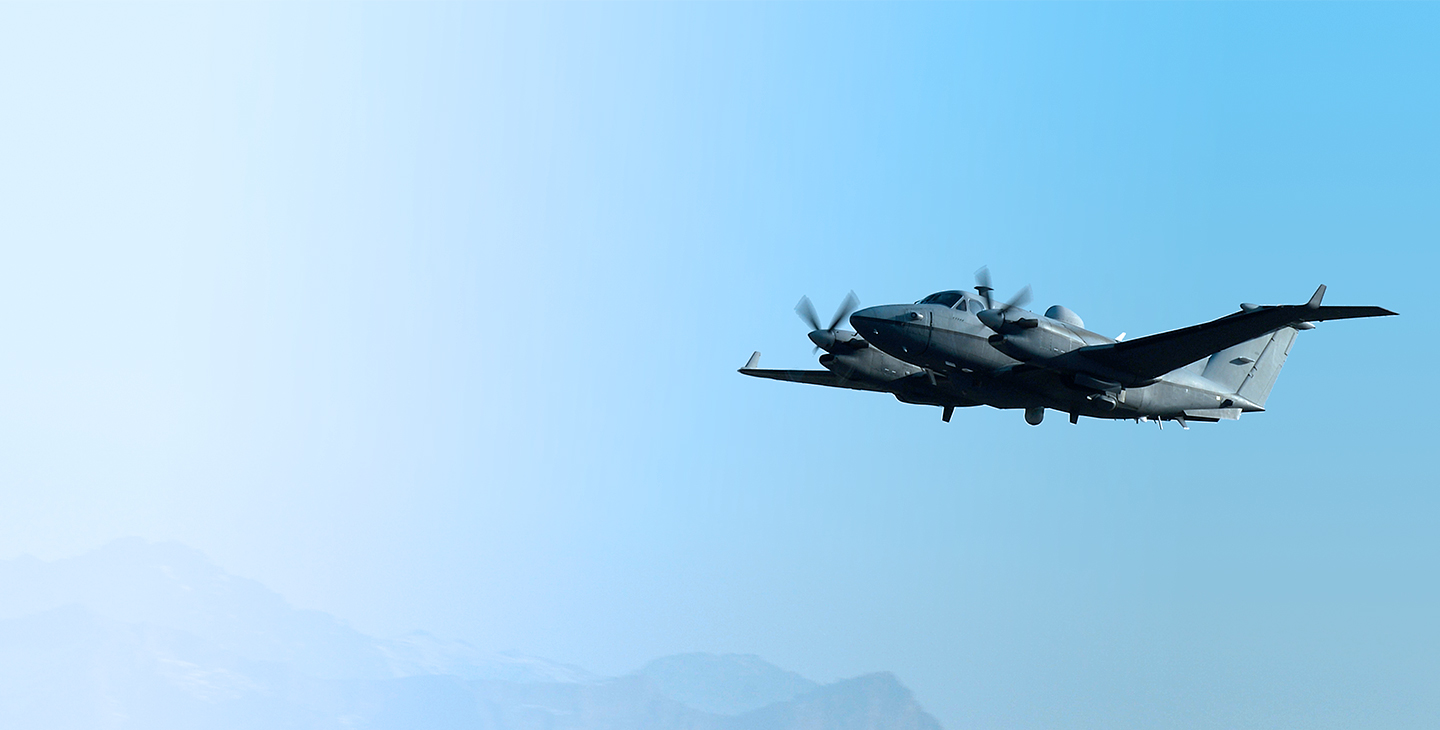 MC-12 Aircraft flying against a light blue sky