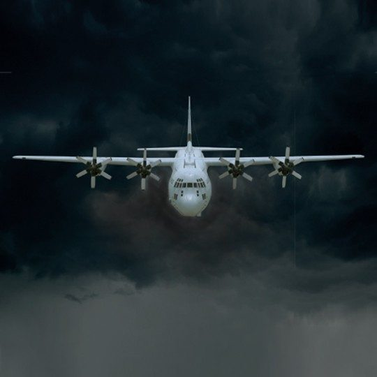 Front view of a C-130J aircraft flying through dark clouds