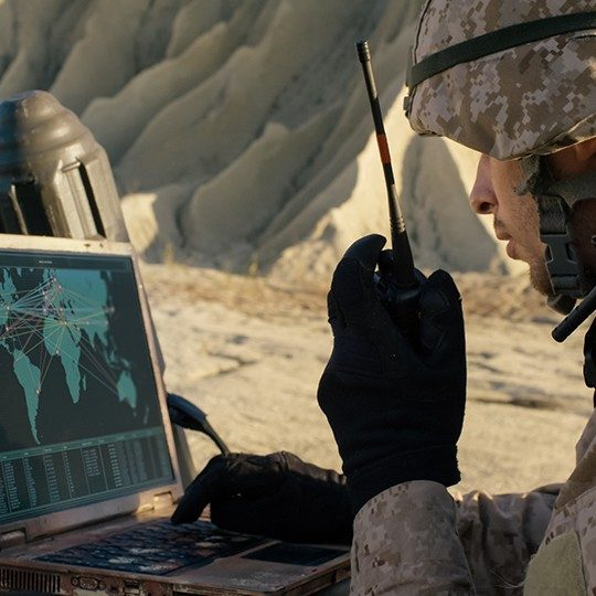 Man dressed in combat gear talking on a radio while looking at a map of the world on a miltary laptop