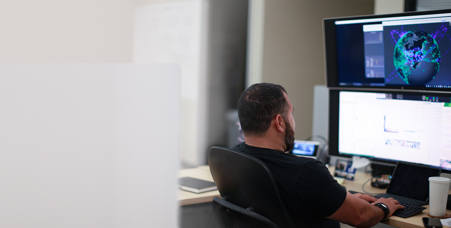 Man sitting at a desk looking at two monitors stacked on top of each other and typing on a keyboard