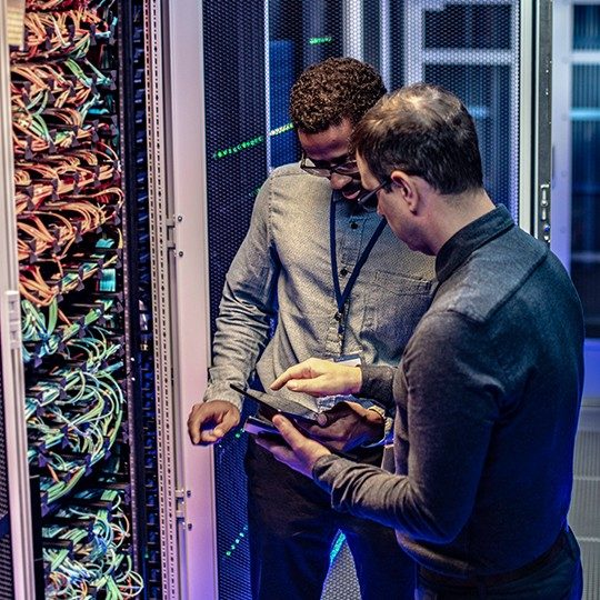 Two men in a server room discussing data protection and looking at a tablet
