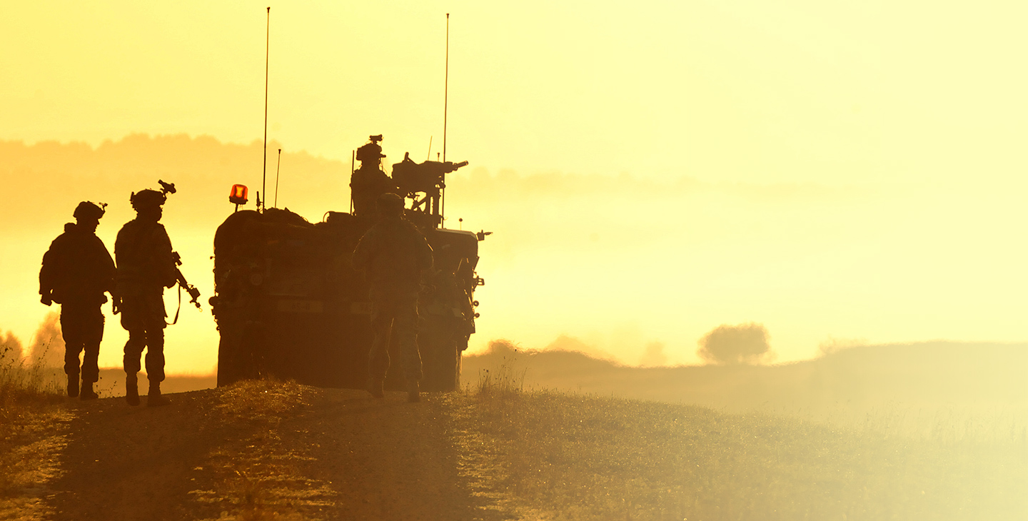 Four soldiers at dusk with a military vehicle utilizing mobile integrated solutions for tactical operations