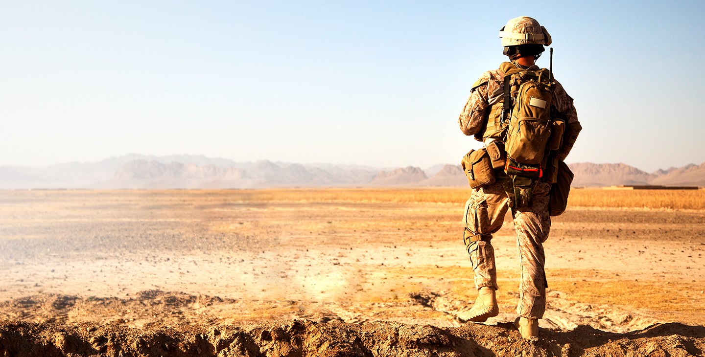 Back of a soldier in the desert, derssed in army gear and backpack