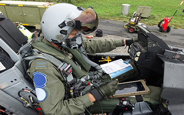 Fighter pilot sitting in a grounded jet looking at a tablet