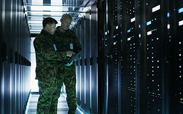 Two men dressed in army greens standing in a server room