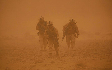 Three soldiers walking through a sand storm
