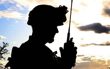 Silhouette of a soldier talking on a handheld radio at disk