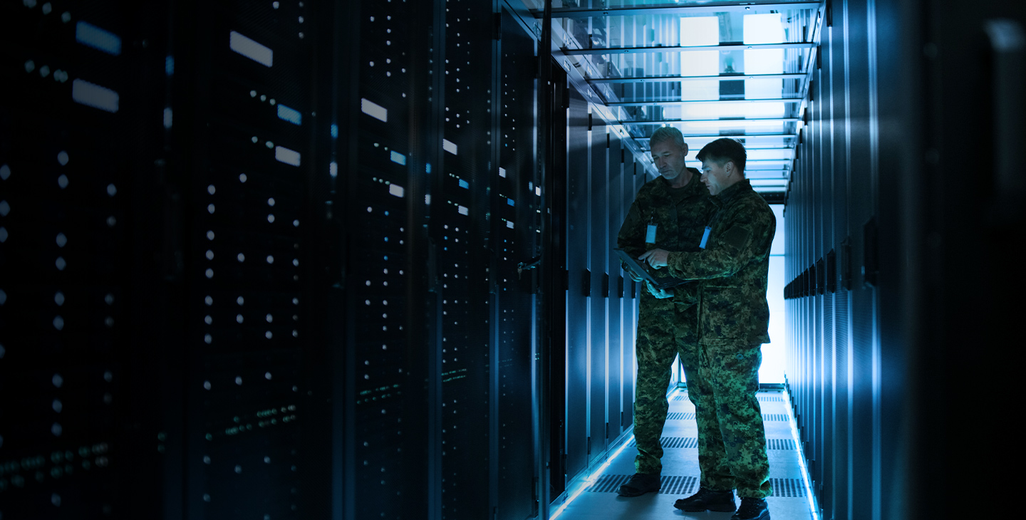 Two men in army uniforms discussing government cybersecurity with a tablet in a server room