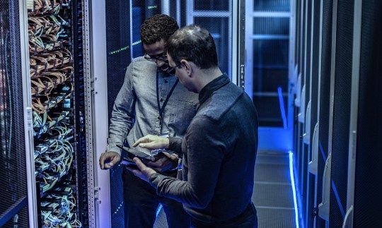 2 men in a server room discussing cybersecurity for government and looking at a tablet