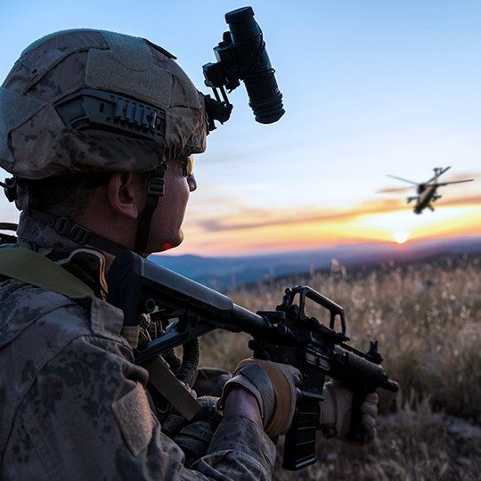 Warfighter standing and looking at helicopter flying away